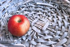 Single Red Apple in a Gray Wicker Basket. Copy Space.  stock photos