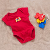 Single red baby bodysuit with plastic toy keys Royalty Free Stock Photo