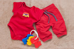 Single red baby bodysuit with plastic toy keys Stock Photo