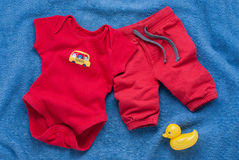 Single red baby bodysuit with plastic toy keys Stock Photos