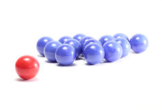 Single red ball and blue balls. Isolated on white background stock photo