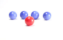 Single red ball and blue balls. Isolated on white background stock images