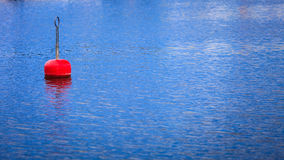 Single red buoy on calm blue sea surface Stock Images