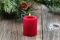 Single red burning Christmas candle with evergreen on rustic woo Royalty Free Stock Photography