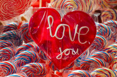 Single red candy lollypop with white text. an i love you lolly with clipping path. Stall with traditional colorful and festive Royalty Free Stock Photography