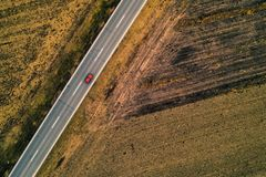 Single red car on the road, aerial view. Single red car on the road, through plain countryside aerial view from drone pov stock images
