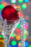 Single red christmas bauble in wineglass on blurred baqckground Royalty Free Stock Photography