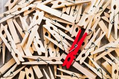 Single red clothespin on a pile of ordinary colored ones/abstract individuality, uniqueness concept.  Stock Photos