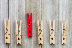 Single red clothespin in a row of ordinary colored ones/abstract individuality, uniqueness concept.  Stock Photography