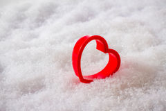 Single red heart in the snow. Top view Stock Photos