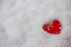 Single red heart in snow. Single red heart in the snow, top view Royalty Free Stock Photography
