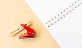 Single Red Hole Punch and Clothespin with Open White Notebook on. Table Surface Stock Image
