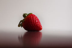 A single, red, organic strawberry. Royalty Free Stock Photos