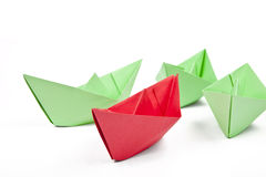 Single red paper boat between lots of green paper Royalty Free Stock Photography