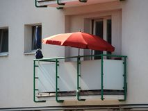 Single Red Parasol on Balcony in Apartment Building Stock Images
