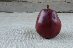 Single Red Pear on Burlap and Wood Background Royalty Free Stock Photos
