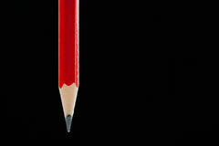 Single red pencil before black Stock Photo