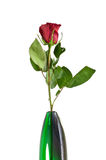 Single Red Rose in Green Glass Vase. A single red rose (Rosaceae) with leaves in an artisan green glass vase stock images
