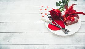 A single red rose with red heart message card on the white dish. Image of dinner on Valentines day Royalty Free Stock Image