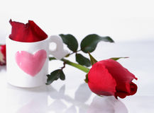 Single red rose with pink heart glass. Stock Photo