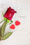 Single red rose with two small red cookies in shape of heart, on Royalty Free Stock Image