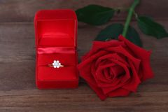 Single red roses and Diamond wedding ring in a red box on wooden background. royalty free stock photo