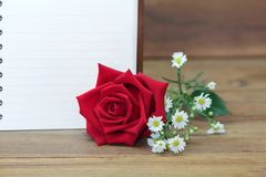 Single red roses and a white book on wooden background. Single red roses and a white book on wooden background, copy space for text Stock Image