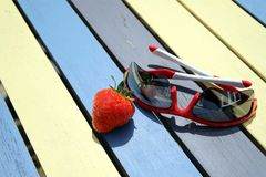 A single red strawberry and a pair of sunglasses stock images