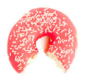 Half eaten red Donut with sugar sprinkles. Single red sugar coated doughnut with sprinkles. Half eaten, bites missing on white background stock photos