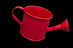 Single Red Watering can Isolated on Black Background tilting dow Royalty Free Stock Photos