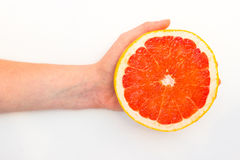 Single ripe fresh grapefruit cut in half isolated over the white background. Ripe fresh grapefruit cut in half isolated over the white background Stock Photos