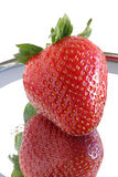 Single ripe strawberry & reflection. 0354. Single strawberry up close-up reflecting on shiny surface. White background Stock Photos