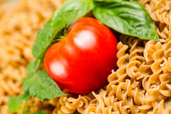 Single Ripe Tomato in pile of uncooked pasta and basil Royalty Free Stock Images