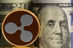 Single Ripple coin in front of bank rolls of US currency Stock Images