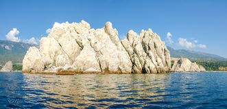 Single rock in the sea against of the mountain shore Royalty Free Stock Photos