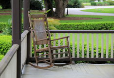 Single rocking chair on country porch. Single rocking chair inviting company to sit for a little while on old country wraparound porch Stock Photography