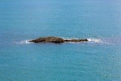 Single rocky island on calm azure blue sea. Stock Photo