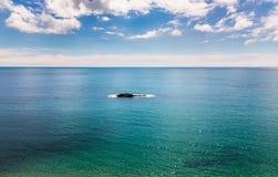 Single rocky island on calm azure blue sea. Royalty Free Stock Photography