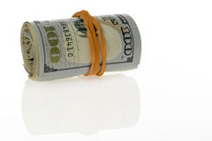 Single Roll Of Hundred Dollar Bills. Laying horizontally, on white background with reflections Royalty Free Stock Photos
