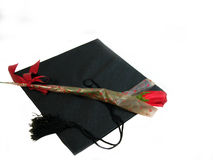 Single Rose graduation. A single rose lieing on a black graduation cap, over white Stock Images