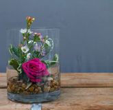 Single Rose Vase Wooden Table. A single hot pink rose bloom in a vase with variagated pitt and wax flower with rocks on a wooden table top bench stock image