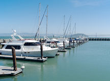 Single row of boats docked in San Francisco on a sunny day. Single row of boats docked in San Francisco Stock Photo