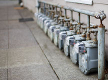 Single Row of gas meters Focus. Row gray gas meters at an apartment complex done with a narrow field of focus Royalty Free Stock Images