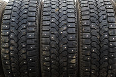 Single row of popular car winter snow tyres with metal spikes for better grip. And safety in snow conditions. Essential transport item for wintery conditions Stock Images