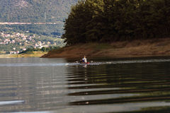 Single rower at sunrise. At the lake Stock Photos