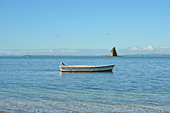Single rowing boat infront of pyramid shaped island Royalty Free Stock Photo