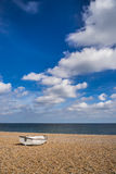 Single rowing boat ona shingle beach facing out to sea Royalty Free Stock Photo