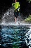 Single runner running, making splash in a stream. Stock Photos
