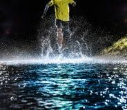 Single runner running, making splash in a stream. Royalty Free Stock Images