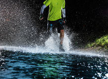 Single runner running, making splash in a stream. Stock Photography